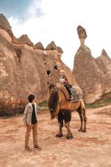 Photo sur Aluminium Vache Traveler couple with camel at Goreme fairy chimneys , Cappadocia. Nevsehir Province. Turkey.