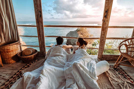 Couple enjoying morning vacations on tropical beach bungalow looking ocean view Relaxing holiday at Uluwatu Bali ,Indonesia