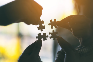 Silhouette image of many people holding and putting a piece of white jigsaw puzzle together
