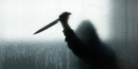 shadow of hand holding big sharp knife behind Frosted glass in the bathroom background.Robber,murderer or killer with knife.concept of scary crime scene of horror or thriller movies,Halloween theme - fototapety na wymiar
