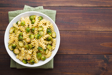 Fresh homemade pasta carbonara with roasted Brussels sprouts and freshly ground black pepper in bowl, photographed overhead with copy space on the right side (Selective Focus, Focus on the dish)