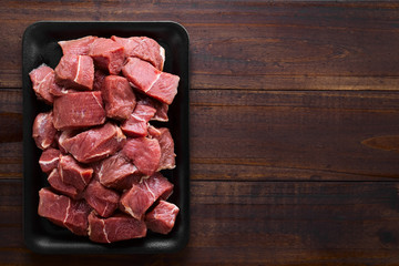 Fresh raw diced red beef meat on cast iron plate, photographed overhead with copy space on the side