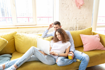 Young happy couple lies on a yellow sofa with a laptop in their apartment, online shopping and internet technology for home