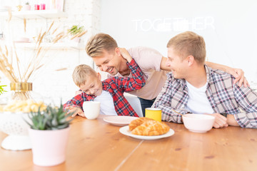 Happy young fathers and son have breakfast in the kitchen, gay family with a child, time together, parenting in homosexual families concept