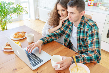 Happy young couple have breakfast in the kitchen and read news on the Internet on a laptop