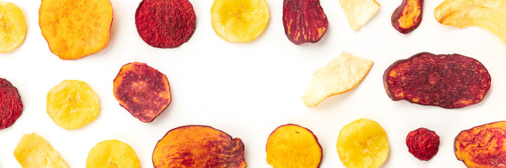 A panorama of dry fruit and vegetable crisps, healthy vegan snack, on a white background, forming a...