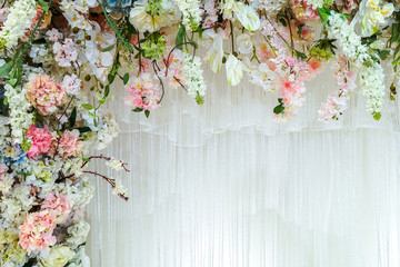 Foto op Plexiglas Bloemen Background of White curtains are adorned with beautiful artificial flowers with copy space.