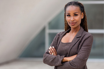 Beautiful female african american business woman CEO in a suit at the workplace, standing confidently with arms folded