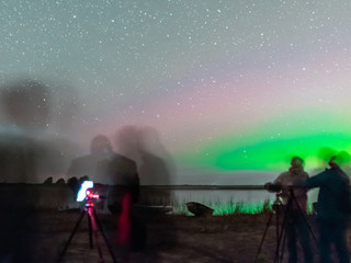 picture with a northern lights on the lake, blurred background.  fuzzy and moving human silhouettes in the foreground