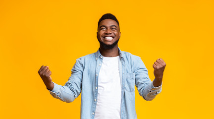Joyful black guy rejoicing success with clenched fists Fotobehang