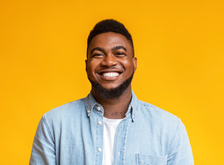 Portrait of cheerful bearded black man over yellow background
