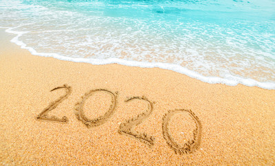 Happy New Year 2020, lettering on the beach with wave and  blue sea. Numbers 2020 year on the sea...