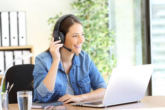 Happy tele operator attending call looking away