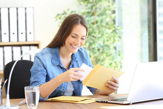 Happy entrepreneur putting document in an envelope