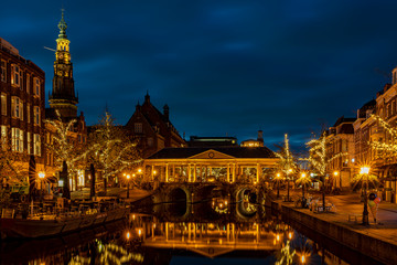 The illuminated Koornbrug, the trees with christmas ornaments and the spire of the town hall in the background during the blue hour, Leiden, the Netherlands