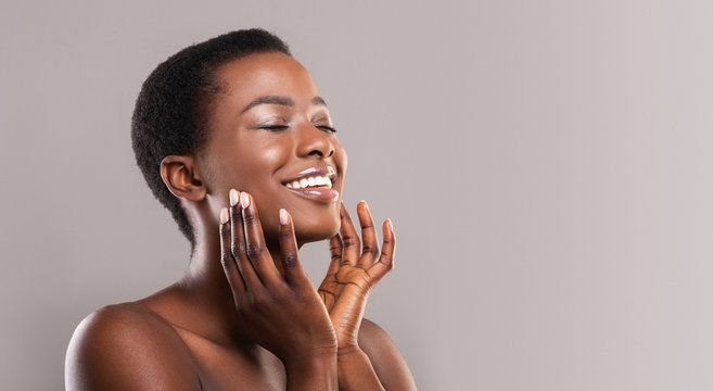 Happy afro woman touching soft smooth skin on her face