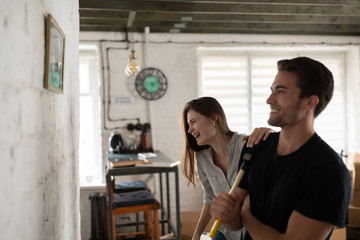 Cheerful couple admiring picture on wall