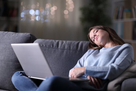 Tired woman with a laptop sleeping in the night