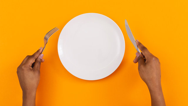 Black female hands holding empty plate on orange background, top view, free space