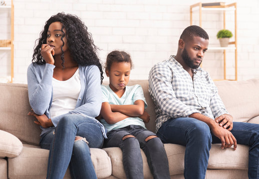 Upset little girl suffer from family conflict, sitting between parents.