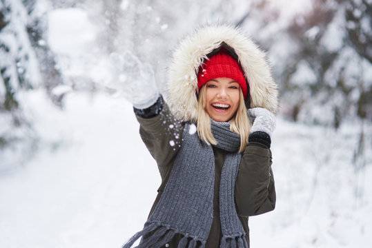 Portrait of playful woman throwing snowball