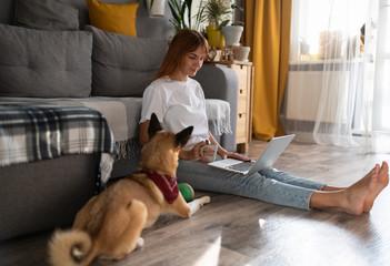 Freelancer with mug using laptop near dog