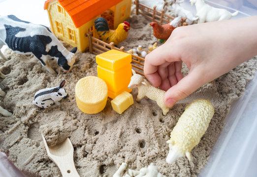 Montessori material. Children's hands play an animal figure. Kinetic sand