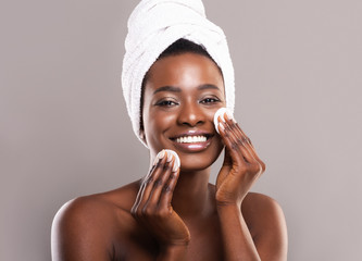 Beautiful black woman cleaning her face with cotton pads