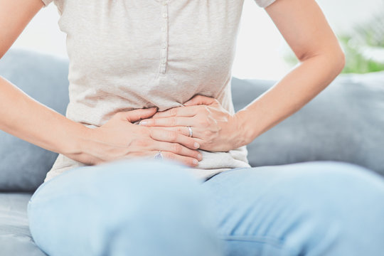 Woman with  stomach issues / problems while lying on the couch.