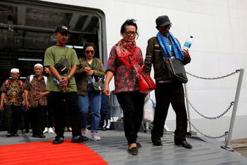 Relatives of passengers who died on Lion Air JT-610 that crashed into the Java sea, arrive at Jakarta International Port after attending one-year commemoration of the crash in Jakarta