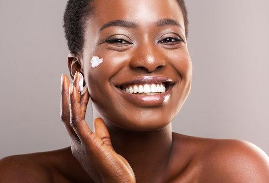 Portrait Of Smiling Black Woman Applying Moisturizing Cream on Face