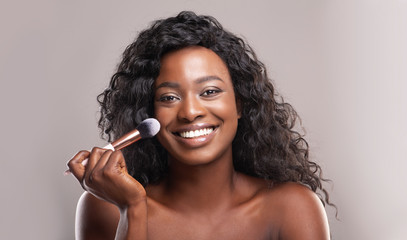 Fototapete - Beautiful african woman applying blush on face with brush tool