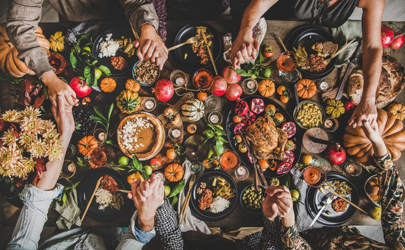 Family praying holding hands at Thanksgiving table. Flat-lay of feasting peoples hands over Friendsgiving table with Autumn food, candles, roasted turkey and pumpkin pie over wooden table, top view
