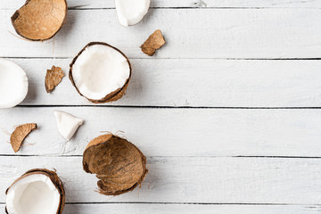Overhead shot of coconut pieces on white wooden background with copyspace. Flat lay
