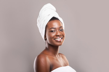 Fototapete - Beautiful black woman with towel on head over grey background