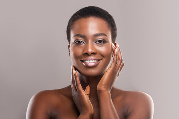 Fototapete - Beautiful black woman with short hair touching her smooth cheeks