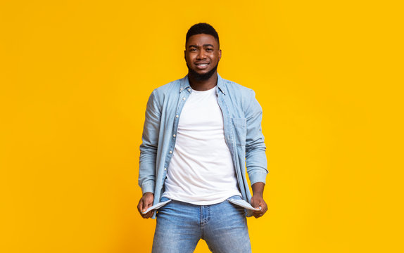 Desperate african american guy showing empty pockets over yellow background