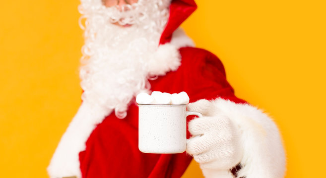 Blurred Santa Claus holding cup with marshmallows over orange