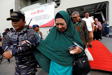 A relative of a passenger who died on Lion Air JT610 crash at the Java sea, is helped by Indonesian navy personnel as she arrives at Jakarta International port after attending one-year commemoration of the crash in Jakarta