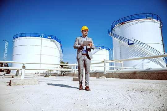 Full length of handsome caucasian businessman in suit standing outdoors and holding tablet. In background are oil storage tanks.