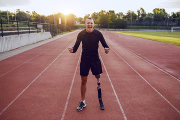 Fotomurales - Sporty handsome caucasian handicapped man with artificial leg standing on racetrack and motivating himself for running.