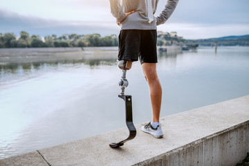 Fotomurales - Rear view of fit healthy Caucasian handicapped man in sportswear and with artificial leg standing on quay with hands on hips.