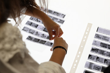 woman cuts 35mm film negatives on a photography lab light table isolated on white closeup organised high quality analog hobby person cinema business laboratory tidy order chemistry studio photo photo