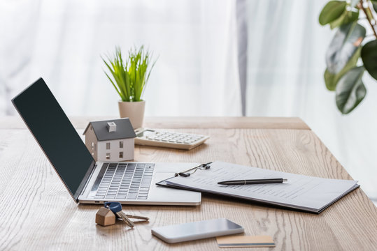 wooden desk with laptop, smartphone, house keys, clipboard with pen, house model and green plant