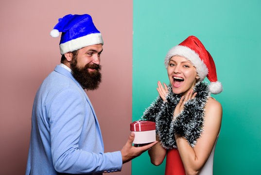 Boxing day. Secret Santa. Winter corporate party. Office christmas party. Christmas party office. Happy man and woman wear santa hats. Cheerful couple celebrate new year. Giving gift. Festive mood