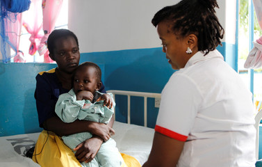 A nurse talks to Apphia Ngunge, whose two year old son, Evans Mwendwa, had his index finger amputated at the Mwingi Level 4 hospital after he was bitten by a snake in Mwingi