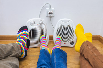 A family dressed in bright socks basks near an electric heaters. Symbolic image of home heating in the cold autumn or winter season. Close-up, selective focus.