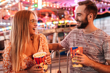 Tuinposter Amusementspark Loving couple walking in amusement park eat popcorn.