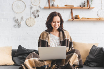 beautiful cheerful girl in blanket using laptop in living room with dream catchers
