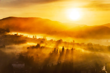 Tuinposter Oranje eclat Bright misty sunrise in a mountain village